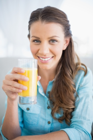 Happy woman holding orange juice smiling at camera
