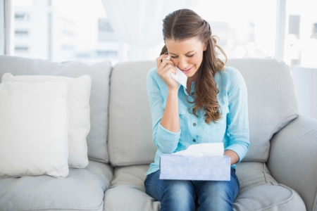 Upset woman crying sitting on sofa in bright living room