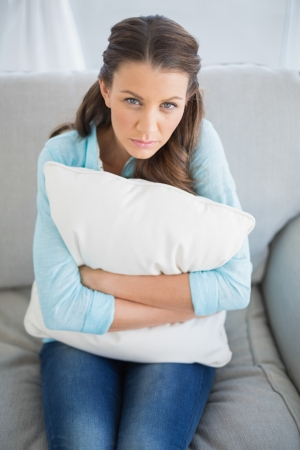 Relaxed woman sitting on sofa holding pillow looking at camera Stock Photo - 22328181