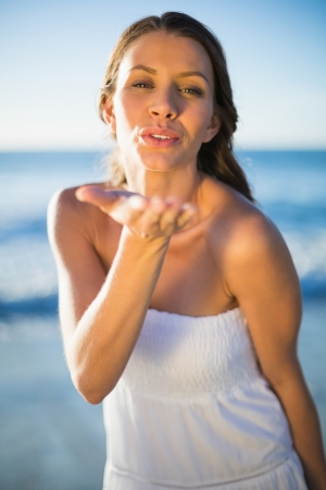 Peaceful brunette in white summer dress on the beach sending air kiss photo