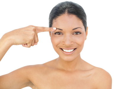 nude black women: Smiling black haired model on white background pointing at her eyebrow Stock Photo