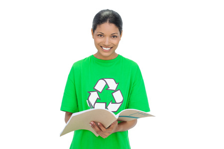Smiling model wearing recycling tshirt holding notebook on white background