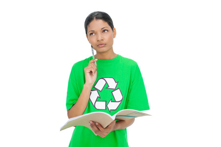 Thoughtful model wearing recycling tshirt holding notebook on white background Stock Photo