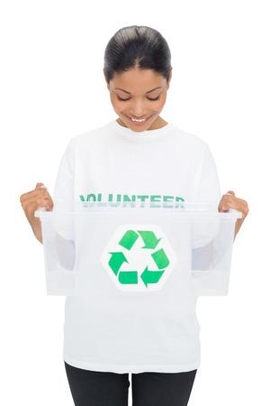 altruismo: Modelo feliz llevando caja de reciclaje holding camiseta voluntario en el fondo blanco