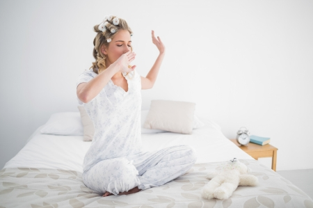 Gorgeous blonde yawning on cosy bed in bright bedroom Stock Photo - 22301704