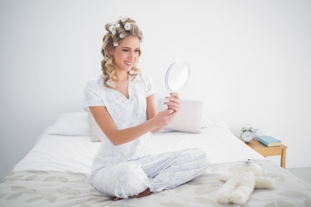 Gorgeous blonde looking at reflection on cosy bed in bright bedroom Stock Photo - 22301705