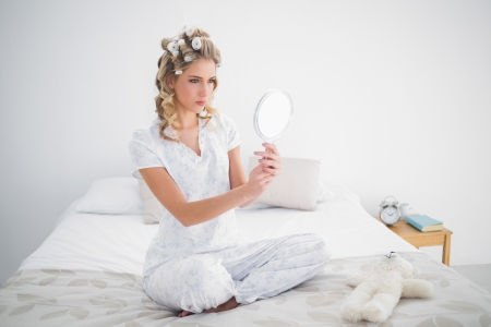 Seus blonde looking at reflection on cosy bed in bright bedroom Stock Photo - 22301707