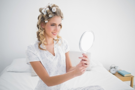 Smiling blonde looking at reflection on cosy bed in bright bedroom photo