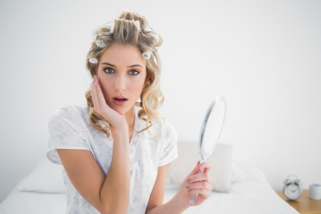taken: Surprised gorgeous blonde wearing hair curlers posing sitting on cosy bed Stock Photo