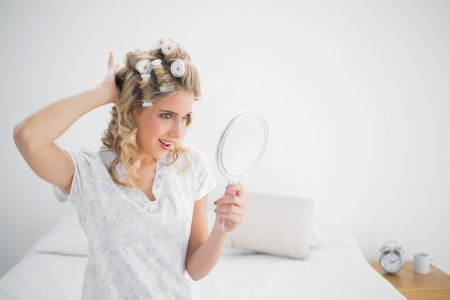 Cheerful gorgeous blonde wearing hair curlers posing sitting on cosy bed photo