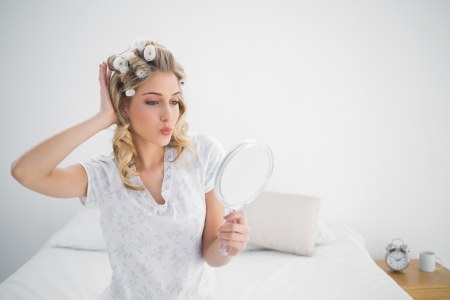 Gorgeous blonde wearing hair curlers kissing while looking at her reflection sitting on cosy bed photo