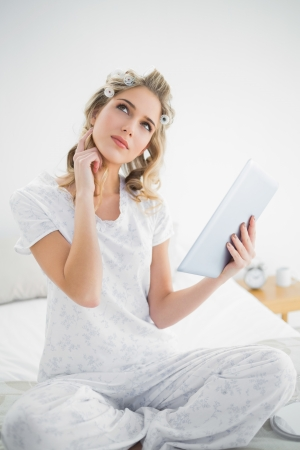 Thoughtful cute blonde wearing hair curlers using tablet sitting on cosy bed photo