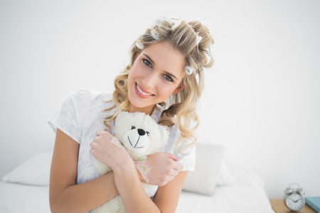 Smiling pretty blonde wearing hair curlers holding teddy bear sitting on cosy bed photo