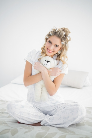 Cheerful pretty blonde wearing hair curlers holding teddy bear sitting on cosy bed photo