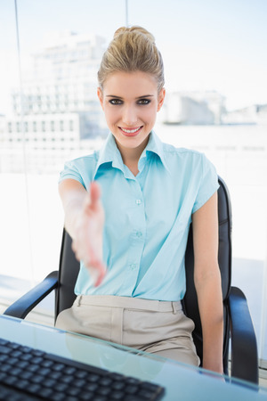 Cheerful classy businesswoman offering hand in bright office photo