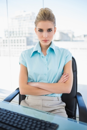 Serious classy businesswoman crossing arms in bright office photo