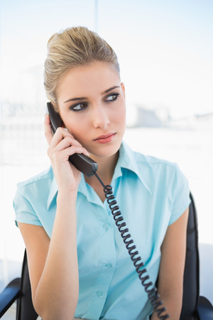 Serious stylish businesswoman on the phone in bright office Stock Photo