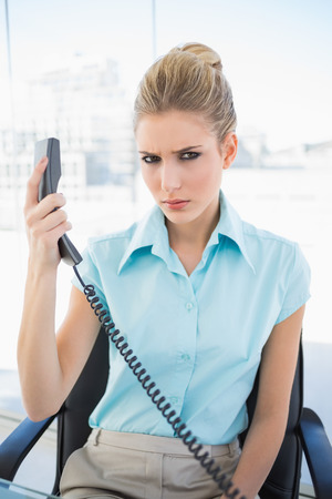 Frowning stylish businesswoman in bright office holding the phone photo