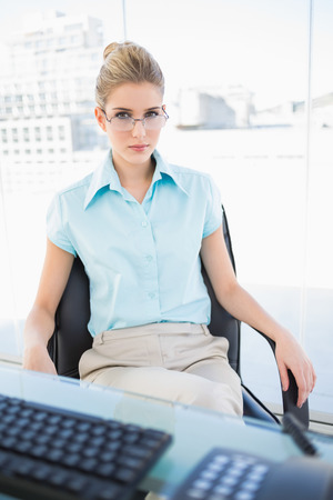 Serious businesswoman wearing glasses posing in bright office