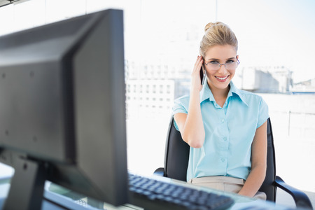 Happy businesswoman wearing glasses having a call in bright office photo