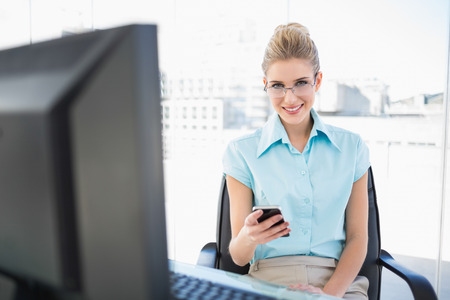 Smiling businesswoman wearing glasses text messaging in bright office photo