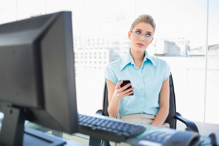 Pensive businesswoman wearing glasses text messaging in bright office photo