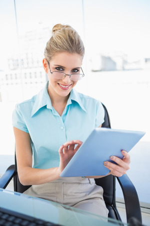 Smiling businesswoman wearing glasses using tablet in bright office photo