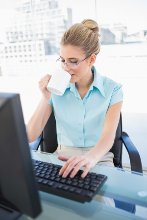 Peaceful elegant businesswoman drinking coffee while working in bright office photo