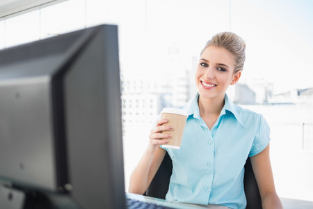 Smiling elegant businesswoman in bright office holding coffee photo