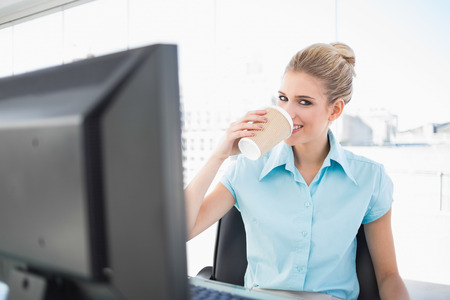 Smiling elegant businesswoman in bright office drinking coffee photo