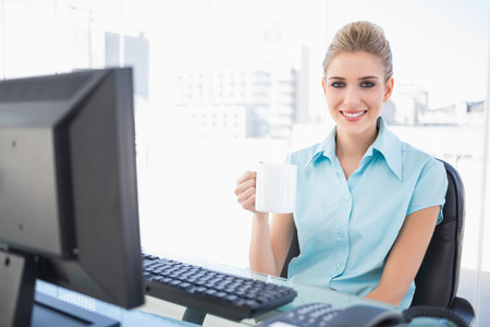 Smiling well dressed businesswoman in bright office holding coffee photo
