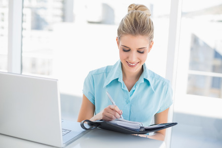 noting: Smiling well dressed businesswoman writing on datebook in bright office