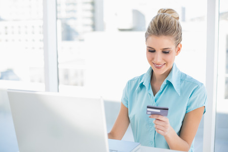 Smiling smart businesswoman in bright office shopping online  photo