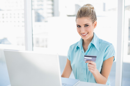 Happy smart businesswoman in bright office shopping online photo