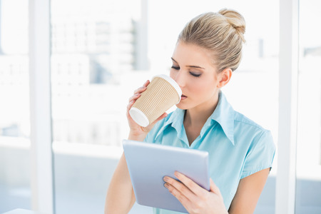 Peaceful classy woman using tablet while drinking coffee in bright office photo