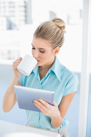 Relaxed elegant woman using tablet while drinking coffee in bright office photo