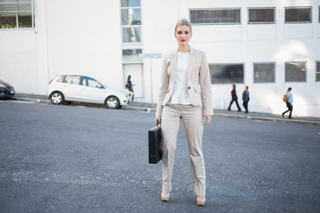Serious stylish businesswoman holding briefcase posing outside on urban background photo