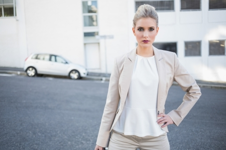 Serious stylish businesswoman posing outside on urban background photo