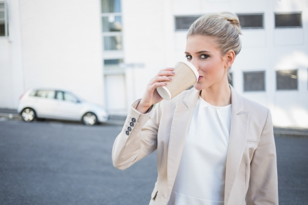 Cheerful stylish businesswoman drinking coffee outside on urban background photo
