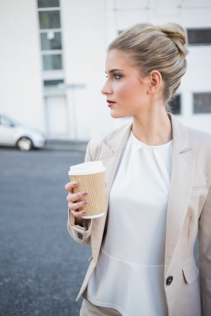 Peaceful stylish businesswoman holding coffee outside on urban background