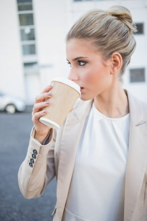 Relaxed stylish businesswoman drinking coffee outside on urban background photo