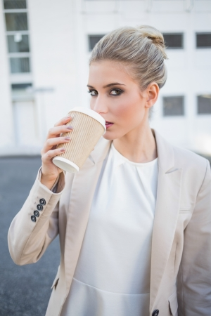 Gorgeous stylish businesswoman drinking coffee outside on urban background photo