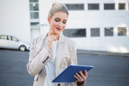 Pensive stylish businesswoman using digital tablet outside on urban background photo