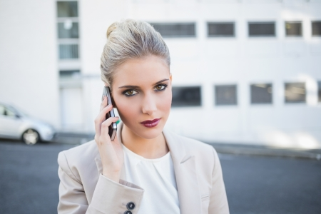 Serious stylish businesswoman having a phone call outside on urban background photo