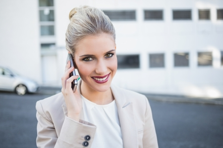 Cheerful stylish businesswoman having a phone call outside on urban background photo