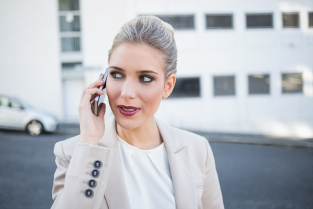Pensive stylish businesswoman having a phone call outside on urban background Stock Photo - 22302153