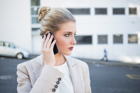 Thoughtful stylish businesswoman having a phone call outside on urban background Stock Photo - 22341410
