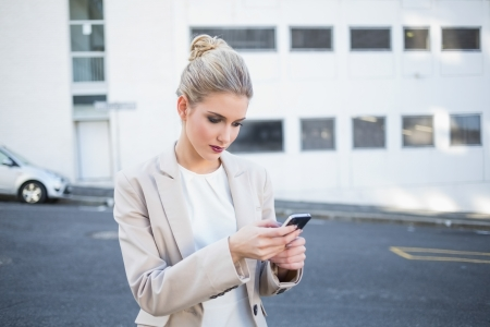 Thoughtful stylish businesswoman sending a text outdoors on urban background Stock Photo - 22341411