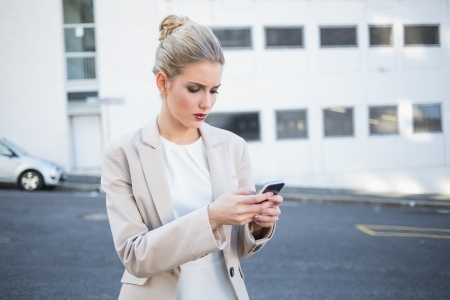 Frowning stylish businesswoman sending a text outdoors on urban background photo