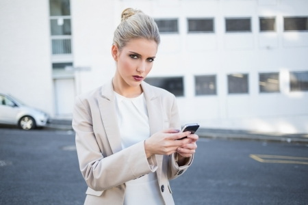 Serious stylish businesswoman sending a text outdoors on urban background Stock Photo - 22341412